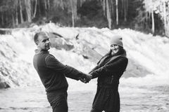Couple in Love Warm Handclasp. Couple in Love on Autumn River Beach over small Waterfall Royalty Free Stock Photo