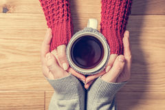 A couple in love warming hands with a hot mug of tea. Wearing cosy woollen jumpers Stock Image