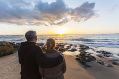 Couple in love watching a sunset on the beach Stock Images