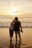 Couple in love watching a sunset at the beach together Royalty Free Stock Photos