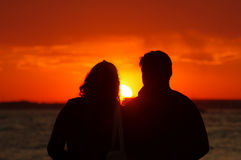 Couple in love watching sunset Stock Photo