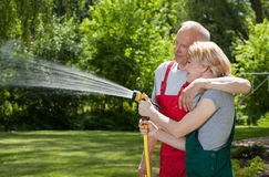 Couple in love watering grass Stock Image