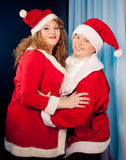 Couple in love wearing Santa hats near Christmas tree. Fat woman and slim  fit. Happy mature couple in love wearing Santa hats near Christmas tree. Fat women and Stock Image