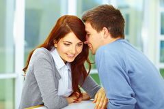 Couple in love whispering something. Handsome men whispering something to his girlfriend and she is listen to him and smiling Stock Image