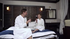 Couple in love in white bathrobes sitting on a wide bed drinking red wine from wine glasses. Family leisure. stock video footage