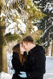 Couple in love in the winter sunny forest. Embrace Stock Photo
