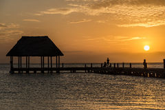 Couple in love at a wooden pier palapa enjoying Sunset at Holbox Stock Photo
