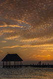 Couple in love at a wooden pier palapa enjoying Sunset at Holbox island near Cancun, Traveling Riviera Maya. Mexico adventure. Couple looking at the sun going royalty free stock images