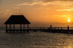 Couple in love at a wooden pier palapa enjoying Sunset at Holbox. Couple looking at the sun going down on a wooden pier with a hut Royalty Free Stock Photography