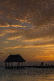 Couple in love at a wooden pier palapa enjoying Sunset at Holbox Royalty Free Stock Photos