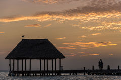 Couple in love at a wooden pier palapa enjoying Sunset at Holbox Royalty Free Stock Photography