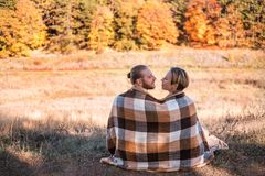 Couple in love wrapped in plaid outdoors. royalty free stock images