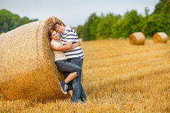 couple in love on yellow hay field on summer evening. Stock Images