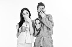 Couple in love, young family in pajama, bathrobe stand isolated on white background. Perfect morning concept. Girl with. Coffee cup, man hold clock in hand and stock photography