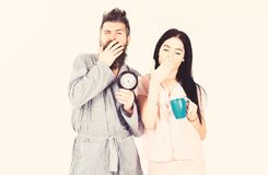Couple in love, young family in pajama, bathrobe stand  on white background. Perfect morning concept. Girl with. Coffee cup, men hold clock in hand and yawning royalty free stock images