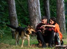 Couple in love or young happy family spend time together. Couple with german shepherd dog on leash near bonfire, forest background. Woman, men and dog on stock photos