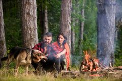 Couple in love or young happy family spend time together. Man play, pat german shepherd dog near bonfire, nature background. Best friend concept. Woman, men stock image