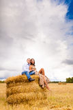 Couple in love young people resting on the haystack Stock Images