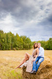 Couple in love young people resting on the haystack Stock Photos