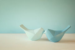Couple of Lovebirds on wooden table. In front of blue pastel background Royalty Free Stock Photography