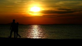 Couple lover walking on beach while sunset on the sea