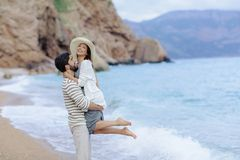 Couple of lovers on the beach. Dressed in warm spring knitted sweaters. Dinner outdoors in the open air. stock image