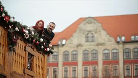 Couple of lovers are cuddling with yourself. They are standing on wooden balcony during Christmas time. Happy new year. Concept. HD, good mood, love, happy stock video footage