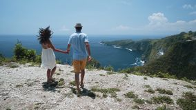 Couple of lovers hand in hand go to cliff look at view of ocean, slow motion. Backside view, couple of lovers hand in hand go to cliff look at beautiful view of stock footage