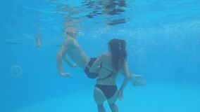Couple of lovers have fun together and swim under the water in a blue swimming-pool on background sparkling bubbles. At summer season stock footage