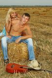 Couple of lovers in the hay with guitar Stock Photography