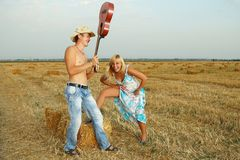 Couple of lovers in the hay with guitar Royalty Free Stock Images