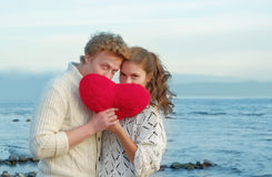 Couple of lovers hojding felt heart in Valentine day/ Sea cost o Stock Photos