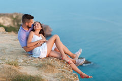 Couple lovers. Hugging couple lovers sitting over beautiful landscape. Romantic date men and women Royalty Free Stock Photography