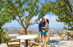 Couple of lovers kissing under trees in a restaurant with panora Stock Photo