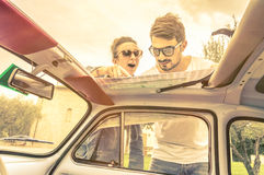 Couple of lovers looking at a map during honeymoon trip vacation Stock Photo