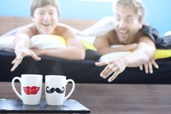Couple of lovers - man and woman just woke up, lie in bed and pull their hands with desire to cups tea or coffee, weekend morning royalty free stock photos