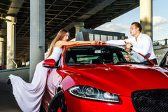 Couple of lovers and red luxury car Royalty Free Stock Images