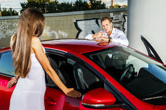 Couple of lovers and red luxury car Royalty Free Stock Photos