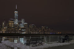 Couple of lovers, sitting on the bench and looking on Manhattan night skyline Royalty Free Stock Image