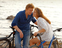 Couple of lovers sitting on the bikes on the coast at sunset Stock Image
