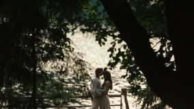 Couple of lovers softly embracing on the pier with chimerical patterns of branches on foreground. Magic love story in stock video footage