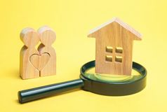 A couple of lovers is standing near the house and a magnifying glass. The concept of finding an apartment or house. Affordable. Housing for young families royalty free stock photography