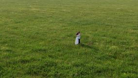 A couple of lovers stands in the middle of a field with green grass. They laugh, dance, kiss and inhale the aroma of