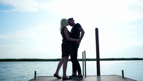 Couple of lovers walking along coast holding each other hand, tender couple kissing in sunlight stock video footage