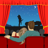 Couple of lovers watching romantic movie in cinema theater Stock Photos