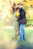Couple loving in the autumn park. Lovers spend sunny day in the autumn park, they hold a bouqet of autumn leaves; blurs around them Stock Images