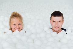 Couple of loving friends have fun surrounded by white plastic balls in a dry swimming pool. Stock Images