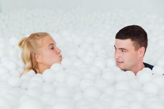 Couple of loving friends have fun surrounded by white plastic balls in a dry swimming pool. Royalty Free Stock Photography