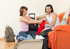 Couple with luggage in home going on holiday. Positive couple with luggage in home going on holiday Royalty Free Stock Images