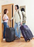 Couple with luggage looking in mirror near door Stock Image